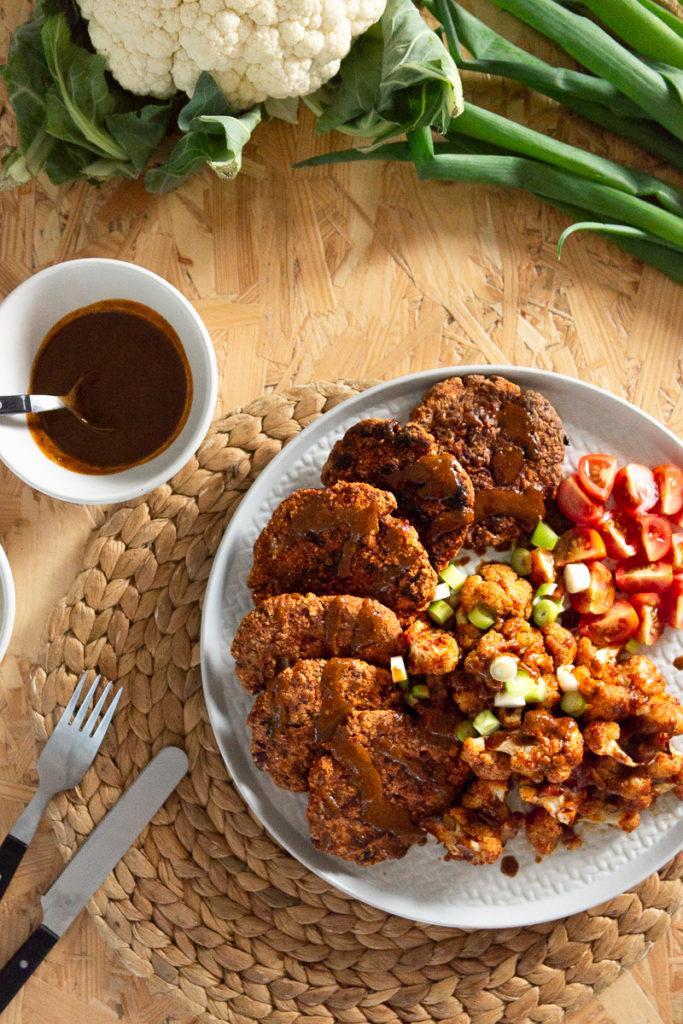 Hier treffen deftige Blumenkohlwings mit gesunden, würzigen Kidneybohnen-Bratlingen zusammen und werden mit einer leckeren Mandel-Sojasaucen-Creme garniert. Ein einfaches und gesundes veganes Rezept für ein leckeres Abendessen. Klick dich gleich zum Rezept!